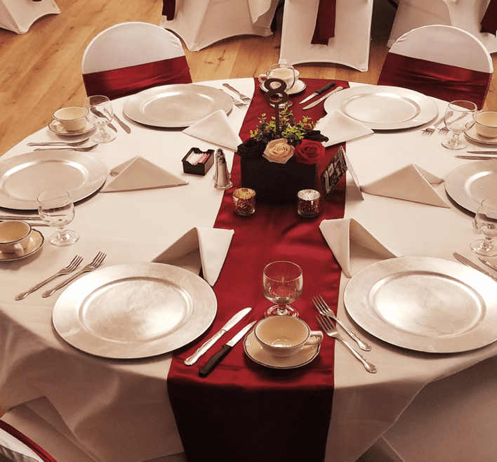 restaurant dining table with plates, glasses, and linen on display