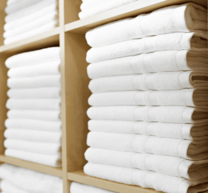 Clean laundry towels are on a laundry towel rack and laundry shelf