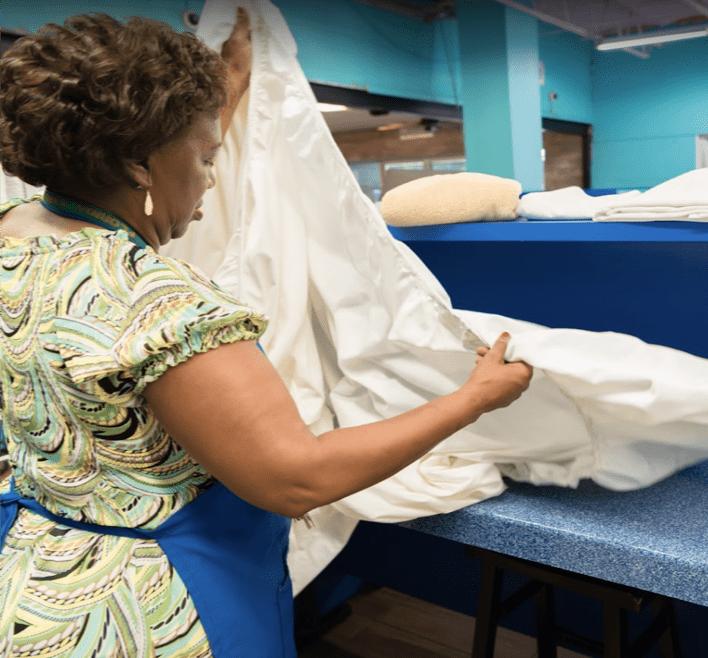 Woman folding laundry at 24 hour laundromat